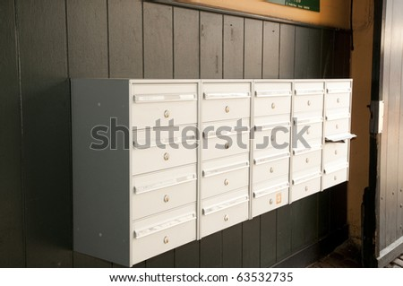 mailboxes against wooden paneling - stock photo