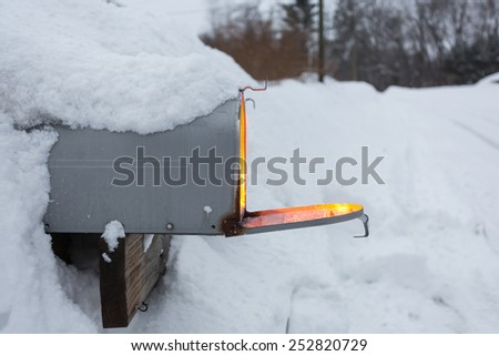 Mailing Sunshine concept shot of a mailbox buried in a snowstorm with warm glowing light - stock photo