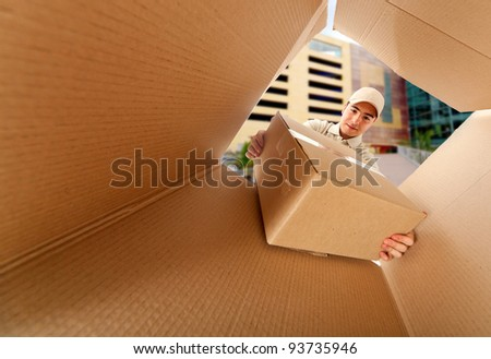 Mailman delivering a package inside a mailbox - stock photo