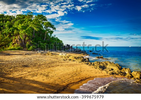 Main beach in Palm cove with rocks and trees during sunset, Australia - stock photo