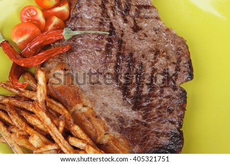 main course : grill beef steak with potato chips and fresh cherry tomato , dry red hot chili peppers on green plate isolated on white background - stock photo