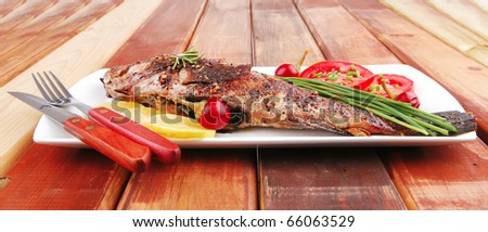 main course on wood: whole fried sunfish on plate with lemons and peppers - stock photo