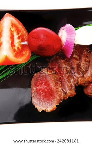 main course : roast red meat slices served on black plate with vegetables on spit isolated on white background - stock photo