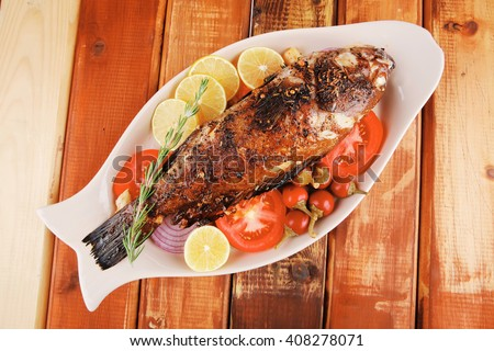 main course: whole fryed sunfish on wooden table with lemons and peppers - stock photo