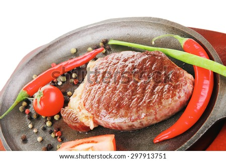 main entree : platter of roasted beef steak served with hot cayenne peppers cherry tomato green chives on metal pan isolated over white background - stock photo