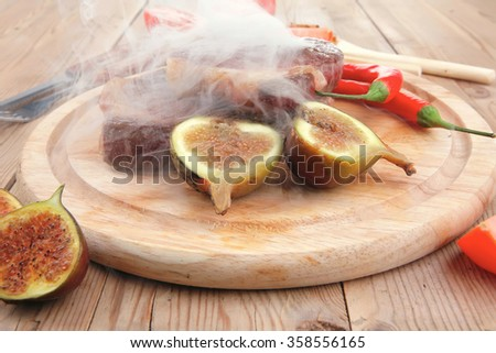main entree : roasted beef lamb steak served with hot cayenne peppers green stuff sweet figs and cutlery on wood plate over wooden table - stock photo