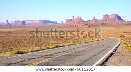 Main highway leading to tall monoliths, buttes, mesas and rock formations in the northern Arizona desert inside the Navajo Indian Reservation around Monument Valley - stock photo