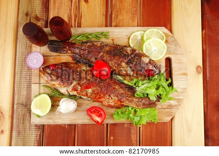 main portion of two grilled fish served on wooden table with castors - stock photo