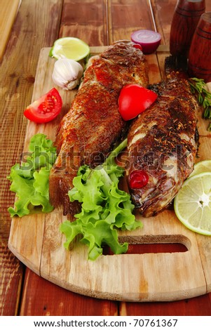 main portion of two grilled fish served on wooden table with castors . shallow dof - stock photo