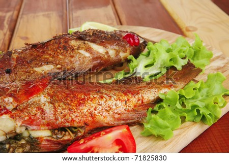 main portion of two grilled fish served on wooden table with castors . shallow dof