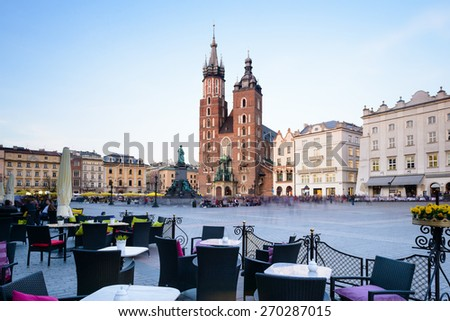 Main Square in Krakow, Poland.  Lovely restaurant next to the Mariacki Church in a beautiful warm light. - stock photo