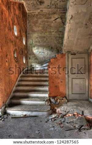 Main staircase and entrance hall in a derelict hotel - stock photo