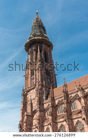Main tower of world famous Freiburg Muenster cathedral, a medieval church in the city of Freiburg, Germany, at the edge of the Black Forest - stock photo