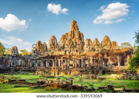 Main view of ancient Bayon temple in Angkor Thom in evening sun. Mysterious Angkor Thom nestled among rainforest in Siem Reap, Cambodia. Enigmatic Angkor Thom is a popular tourist attraction. - stock photo