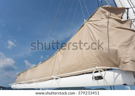 Mainsail of catamaran with blue sky - stock photo