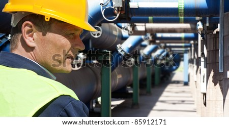 Maintenance engineer at the waste water management system of a huge factory - stock photo
