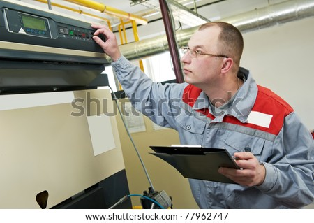 maintenance engineer checking technical data of heating system equipment in a boiler house
