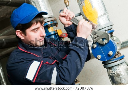 maintenance engineer of heating system with adjustable wrench spanner equipment in a boiler room - stock photo