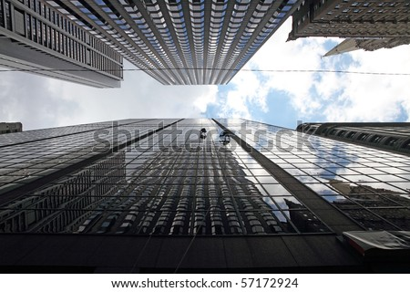 Maintenance workers climbing outside a skyscraper and clean windows - stock photo