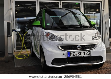 MAINZ,GERMANY-FEB 20:green energy and white Smart Car on February 20,2015 in Mainz, Germany.Smart Automobile is a division of Daimler AG that manufactures and markets the Smart Fortwo. - stock photo