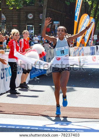 MAINZ, GERMANY - MAY 8: Asha Gigi Roba of Ethopia crosses the finish line to win the Gutenberg Marathon on May 8, 2011 in Mainz, Germany. 9,500 runners participate in the event. - stock photo