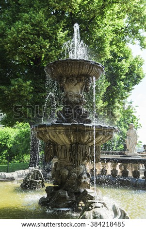 Majestic antique stone fountain in the courtyard of an ancient german castle surrounded by green summer trees located in Dresden, Germany. - stock photo