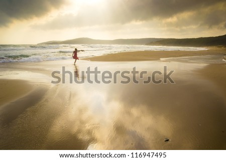 Majestic beach with dramatic reflections and girl running freely - stock photo