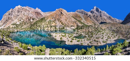 Majestic blue mountain lake with juniper on the shore in Tajikistan - stock photo