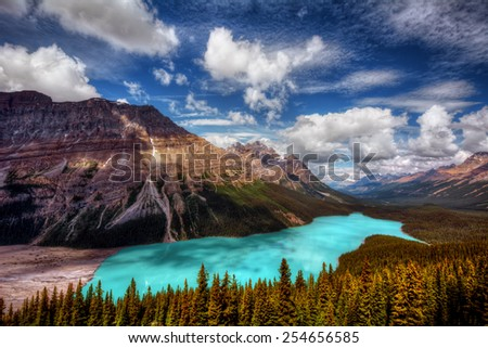 Majestic clear lake with mountain in view and evergreen trees in the foreground - stock photo