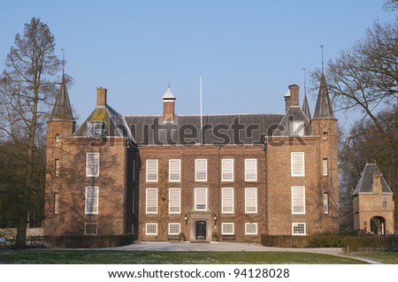 Majestic Dutch castle in the winter with hoarfrost on the lawn. Nobility and aristocracy lived the rural life in this manor with two stately towers.