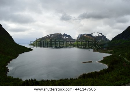 majestic fjord and mountain landscape in northern norway on a cloudy summer day - stock photo