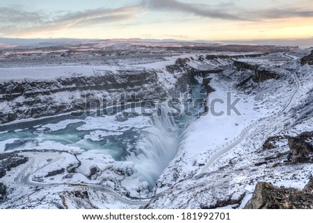 Majestic Gullfoss falls into a wintry gorge agt sunset in Western Iceland - stock photo