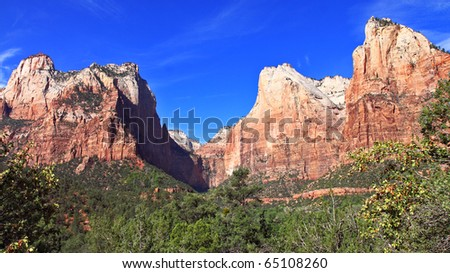 Majestic jagged mountain peaks of red, orange, white and coral colored sandstone and shale tower over lush green valley at Zion National Park - stock photo