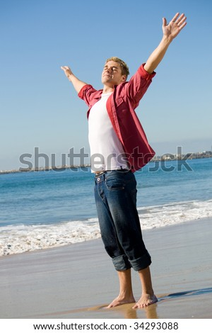 majestic man with arms outstretched on beach - stock photo