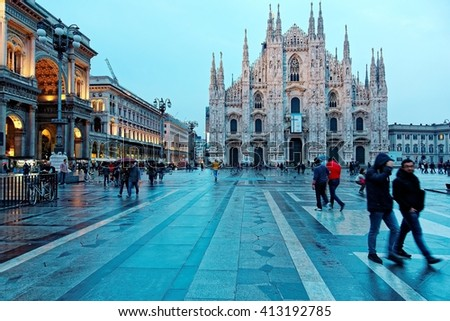 Majestic Milan Cathedral (Duomo di Milano) & Piazza del Duomo in evening light, Milan, Italy ~ Night view of Milan Cathedral  & Vittorio Emanuele II Gallery at dusk with tourists walking in the square - stock photo
