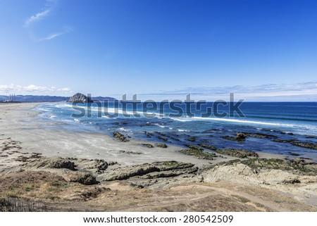 Majestic Morro Rock over looking the Pacific Ocean, next to Morro Strand state beach, on the California Central Coast, near Cambria, CA. - stock photo