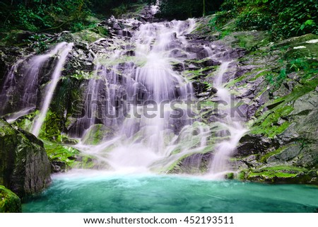 Majestic moss covered waterfall in tropical rainforest - stock photo