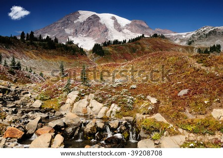 Majestic Mount Rainier blushing with valleys covered with fall colors - stock photo