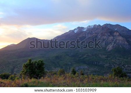 Majestic Mount Timpanogos towers over Utah Valley, Utah, at sunset on a spring evening. - stock photo