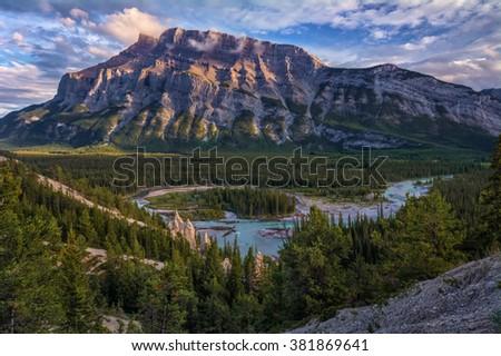 Majestic mountain, turquoise river snaking through the dense trees - stock photo