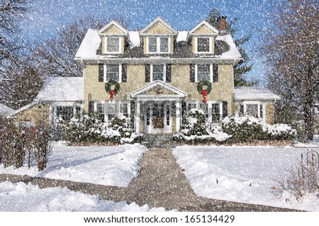 Majestic Newly Constructed Home Facade with Giant Christmas Wreaths on a Snowing Blustery Day. - stock photo
