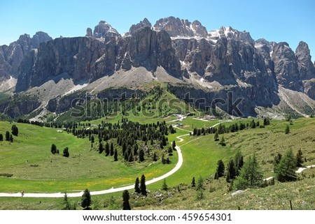 Majestic north face of rugged Sella group & hiking trails in green grassy valley as seen from Mountain Cir on a sunny summer day in Pass (Val) Gardena, Dolomiti, Bolzano, Trentino, South Tyrol, Italy - stock photo