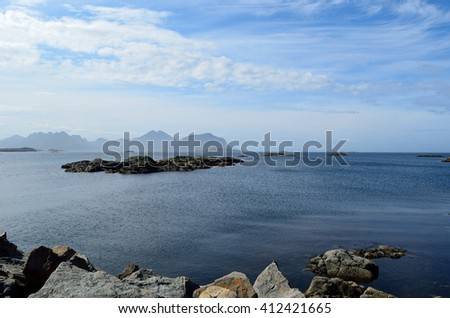 Majestic ocean landscape with many small rocky islands and mountain backdrop - stock photo