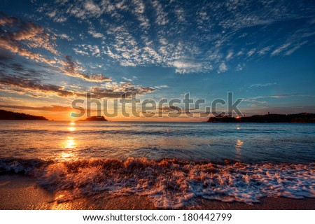 Majestic ocean sunset with a breaking wave - stock photo