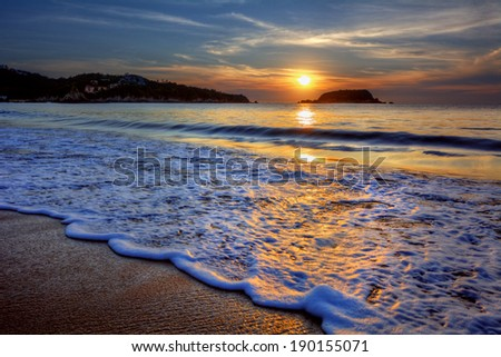 Majestic ocean sunset with a breaking wave 3 - stock photo