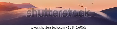 Majestic panorama of mountains at sunrise with pack of flying birds. - stock photo