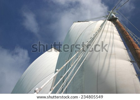 Majestic sails are full of wind against a mostly clear sky - stock photo