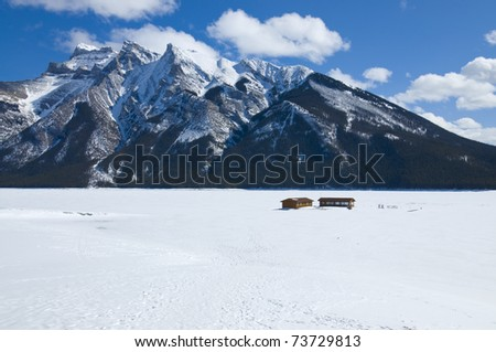 Majestic Sceneic of the frozen Lake Minnewanka, Banff National Park, Alberta, Canada. Fueling station gas pumps pertruding in the thick ice and snow. - stock photo