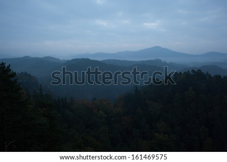 Majestic shot of trees and mountain range against cloudscape