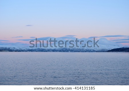 majestic snowy mountain with colorful sunset sky and beautiful cloud formation with cold fjord water underneath in wintertime